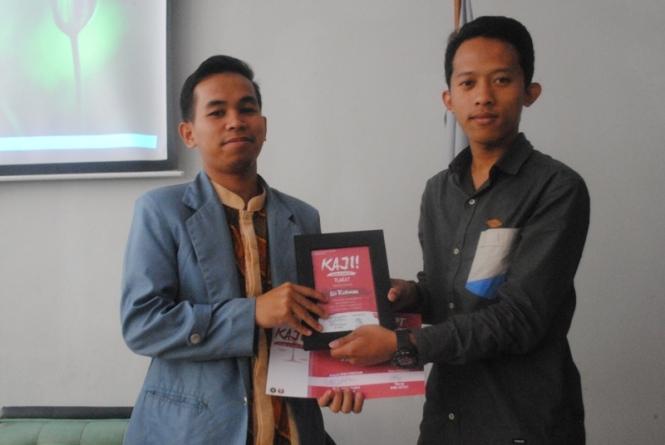 Pemberian plakat dan sertifikat pada Ali Rohman oleh Arif Husni selaku Presiden BEM KEMAKOM.