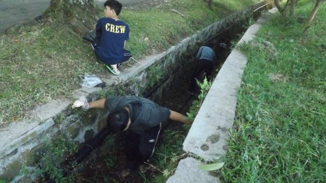 Sedang membersihkan sampah di selokan Lapangan Berdebu UPI.