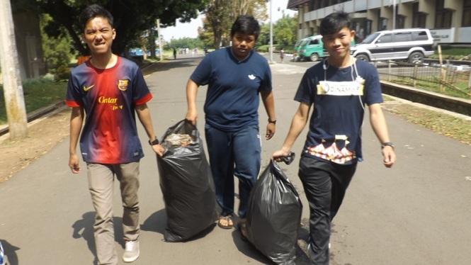 Banyu, Agung, dan Yudo membawa trashbag sampah terakhir.